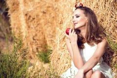 美丽的微笑的女孩佩带的白色夏天坐在干草堆和拿着一个红色苹果的礼服和花卉顶头花圈 库存照片