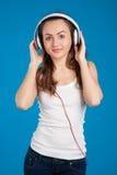 美丽的微笑的女孩听的音乐佩带的白色耳机 免版税库存照片