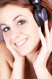 美丽的微笑的女孩听的音乐 图库摄影