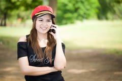 美丽的微笑的女孩在手机联系户外 免版税库存图片