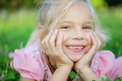美丽的微笑的女孩在绿草说谎 库存照片