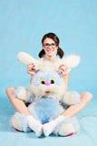 美丽的微笑的女孩坐用一只软的玩具兔子 免版税库存图片
