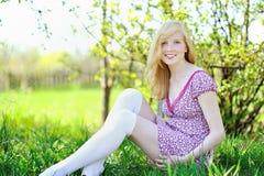 美丽的微笑的女孩坐草在公园 库存照片