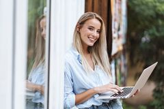 美丽的微笑的女孩藏品手提电脑 免版税库存照片