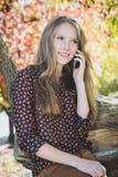 年轻美丽的微笑的女孩谈话在手机在公园 免版税库存图片
