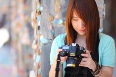 美丽的微笑的女孩画象,有数字照相机的在她的手上 免版税库存图片