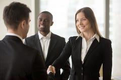 美丽的微笑的女实业家和商人握手,冷杉 免版税库存照片