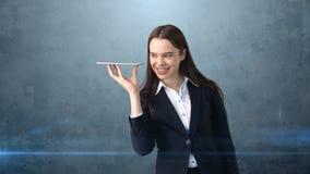 美丽的微笑的女实业家拿着盘子并且看某事 免版税库存图片