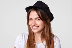 美丽的微笑的女性射击的关闭有欧洲出现的戴典雅的帽子,并且白色T恤杉,为时装杂志摆在 免版税图库摄影
