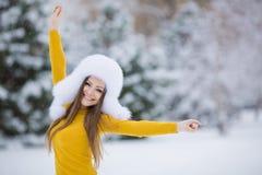 美丽的微笑的妇女冬天画象有雪花的在白色毛皮 免版税库存图片