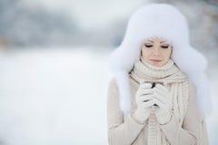美丽的微笑的妇女冬天画象有雪花的在白色毛皮 免版税图库摄影