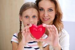 美丽的微笑的妇女和孩子拿着红色玩具心脏 库存图片
