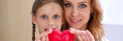 美丽的微笑的妇女和孩子拿着红色玩具心脏 免版税库存图片
