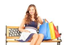 美丽的微笑的妇女坐与袋子的一个长木凳 免版税库存照片