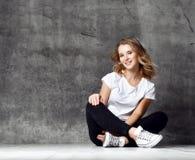 美丽的微笑的妇女坐地板对混凝土墙 库存照片