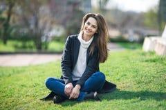 美丽的微笑的妇女坐室外的草 免版税图库摄影