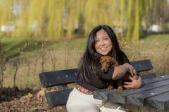 美丽的微笑的妇女坐拥抱小狗的长凳 免版税库存图片