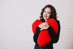美丽的微笑的妇女用红色心脏手在情人节 图库摄影