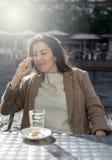 年轻美丽的微笑的妇女谈话在手机 免版税库存图片