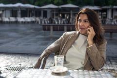 年轻美丽的微笑的妇女谈话在手机 库存图片