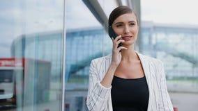 美丽的微笑的妇女谈话在电话在营业所附近 股票录像