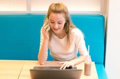 美丽的微笑的妇女画象坐在一个咖啡馆的一把舒适的椅子与黑膝上型计算机 完成与膝部一起使用的俏丽的学生 图库摄影