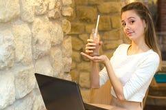 美丽的微笑的妇女画象坐在一个咖啡馆的一把舒适的椅子与黑膝上型计算机和饮用的新鲜的汁液戒毒所 前 库存照片