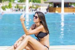 美丽的微笑的妇女画象谈话在电话坐水池 免版税库存照片