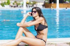 美丽的微笑的妇女画象谈话在电话坐水池 免版税图库摄影