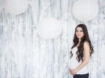 美丽的微笑的孕妇画象在木白色b的 库存图片