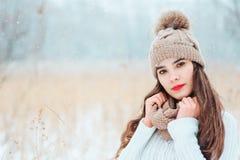 美丽的微笑的少妇冬天接近的画象被编织的帽子和毛线衣走的室外下面降雪的 免版税库存照片