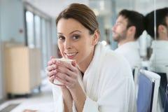 美丽的微笑的少妇在温泉中心的喝热的茶 免版税库存图片
