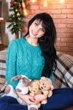 美丽的微笑的少妇坐在圣诞节装饰的沙发 免版税库存图片