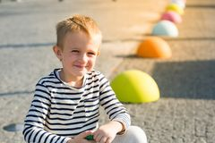 美丽的微笑的愉快的小男孩坐色的石头,看照相机 库存图片