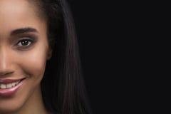美丽的微笑的敏感美国黑人的妇女半面孔画象黑暗的背景的 免版税图库摄影