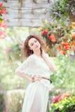 美丽的微笑的白白种人女孩妇女画象有长的深红棕色头发的,在白色夏天礼服 免版税库存图片