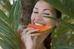 美丽的微笑的白种人妇女用新鲜水果番木瓜(户外) 库存照片