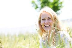 美丽的微笑的白肤金发的妇女在草甸 免版税库存照片