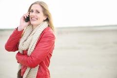 美丽的微笑的白肤金发的妇女联系在电话 免版税库存照片