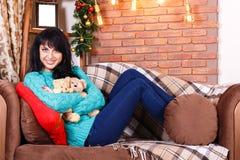 美丽的微笑的西班牙女孩坐在圣诞节12月的沙发 免版税图库摄影