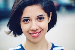 美丽的微笑的年轻拉丁西班牙女孩妇女特写镜头画象有短的深黑色头发突然移动的 库存图片