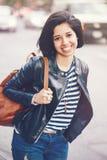 美丽的微笑的年轻白种人拉丁女孩妇女画象有黑褐色的注视,短的黑发,在蓝色牛仔裤,皮革骑自行车的人 库存照片