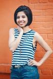 美丽的微笑的年轻行家拉丁西班牙女孩妇女画象有短发突然移动的,在蓝色牛仔裤,镶边了T恤杉 免版税图库摄影