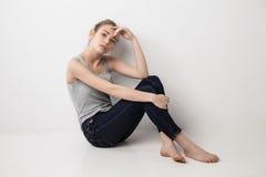 美丽的忧郁的女孩坐地板 免版税库存照片