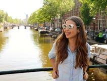 美丽的快乐的女孩画象有看对在其中一种典型的阿姆斯特丹渠道,荷兰的边的太阳镜的 图库摄影