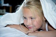 美丽的快乐的女孩从毯子下面看  库存图片