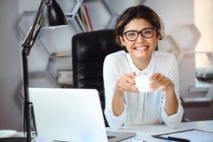 年轻美丽的快乐的女实业家饮用的咖啡,微笑在工作场所在办公室 库存照片