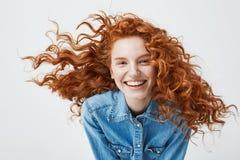 美丽的快乐的红头发人女孩画象有飞行的卷发微笑的笑看在白色的照相机 免版税图库摄影