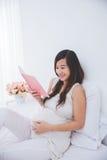 美丽的怀孕的亚洲妇女读书笔记本,微笑 库存图片