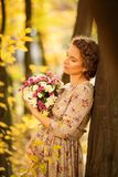 美丽的怀孕的女性在秋天 免版税库存图片